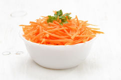 Grated carrot in bowl on white table Royalty Free Stock Photo