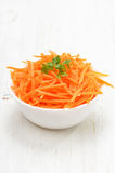 Grated carrot in bowl. On white wooden table Stock Images