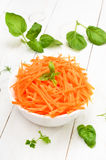 Grated carrot in bowl on white wooden table Royalty Free Stock Images