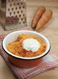 Grated carrot with  sour cream. In an orange bowl Royalty Free Stock Photography