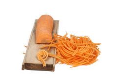 Grated carrot sticks and a wooden grater Stock Photography
