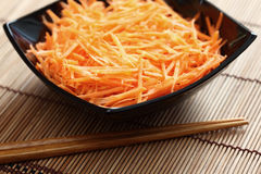 Grated carrots in bowl with chopsticks Royalty Free Stock Photos