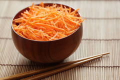 Grated carrots in bowl with chopsticks Stock Image