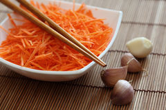Grated carrots in bowl with chopsticks and garlic Royalty Free Stock Photos