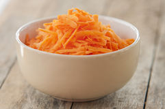 Grated carrots in bowl Royalty Free Stock Photo
