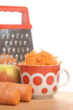 Grated carrots in a cup on a white background Royalty Free Stock Images