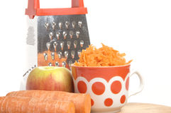 Grated carrots in a cup on a white background Royalty Free Stock Photo