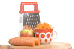 Grated carrots in a cup on a white background Stock Photos