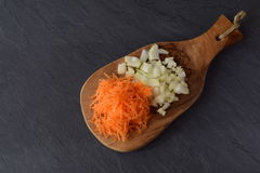 Grated carrots and cut in cubes onion on a olive wood cutting board on a grey abstract background. Step by step cooking. royalty free stock photo