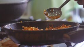 Grated carrots are fried in a frying pan on sunflower indoors oil. vegetarianism grated food carrots. Grated carrots are fried in frying pan on sunflower indoors stock footage