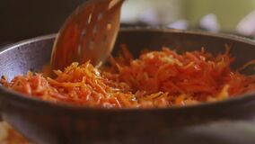 Grated carrots are fried in a frying pan on sunflower oil. vegetarianism indoors grated food carrots. Grated carrots are fried in frying pan on sunflower oil stock video