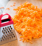 Grated carrots and a small grater Royalty Free Stock Photography