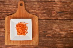 Grated carrots in a white cup on a wooden background. Isolate. Food background. Grated carrots in a white cup on a wooden background. Isolate stock photography