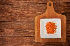 Grated carrots in a white cup on a wooden background. Isolate. Food background. Grated carrots in a white cup on a wooden background. Isolate royalty free stock images