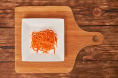 Grated carrots in a white cup on a wooden background. Isolate. Food background. Grated carrots in a white cup on a wooden background. Isolate royalty free stock photography