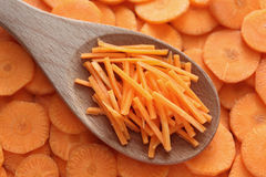 Grated carrots in a wooden spoon. On slices carrot background. Close-up Royalty Free Stock Photo