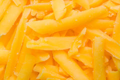 Grated cheddar cheese. Closeup of grated cheddar cheese for background Royalty Free Stock Images