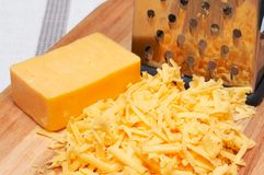 Grated cheddar cheese on wooden board. With grater next to it Stock Photography