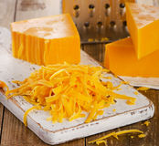 Grated Cheddar Cheese on  wooden Cutting Board. Stock Photo