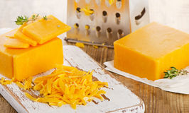 Grated Cheddar Cheese on  a wooden Cutting Board. Royalty Free Stock Photography