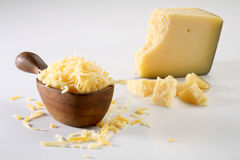Grated cheese. Grated parmesan and gouda cheese with little wood spoon, on back slice with pieces of parmesan cheese Royalty Free Stock Photos