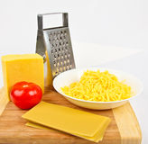 Grated cheese and grater Royalty Free Stock Image