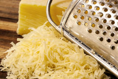 Grated Cheese and Grater on Board Royalty Free Stock Image