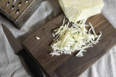 Grated cheese with grater and knife Royalty Free Stock Photography