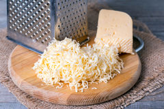 Grated cheese with grater. On a wooden background stock images