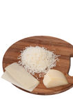 Grated cheese on a kitchen wooden board and cheese in one piece Royalty Free Stock Images