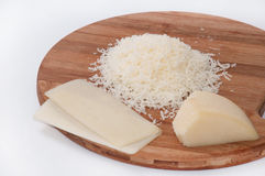 Grated cheese on a kitchen wooden board and cheese in one piece Stock Photo