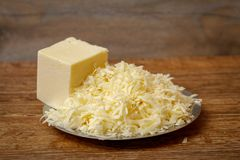 Grated cheese on metal plate on wooden table stock photos