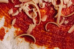 Grated cheese for pizza close up on ketchup coated dough stock images