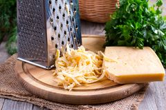 Grated Cheese. On a wooden background Royalty Free Stock Photos