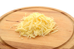 Grated cheese on a wooden board Stock Photos