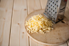 Grated cheese on a wooden board Stock Photography