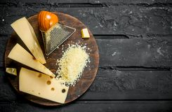 Grated cheese on a wooden Board. On black rustic background royalty free stock photography