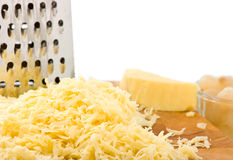 Grated Cheese on wooden board with grater. Royalty Free Stock Photography