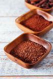 Grated chocolate , cocoa beans, powder  in wooden bowls, white w Royalty Free Stock Photography
