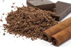 Grated chocolate with spices. Grated chocolate with cinnamon and blocks of chocolate isolated on white Stock Images