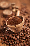 Grated coffee in spoon on roasted coffee  beans Stock Photos