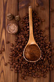Grated coffee in spoon on roasted coffee beans background stock photo