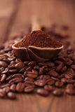 Grated coffee in spoon on roasted coffee  beans background Royalty Free Stock Photo