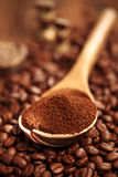 Grated coffee in spoon on roasted coffee  beans background Stock Images