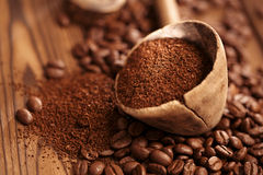 Grated coffee in spoon on roasted coffee  beans background Royalty Free Stock Photos