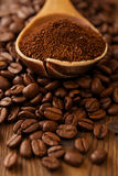 Grated coffee in spoon on roasted coffee  beans background Royalty Free Stock Photography
