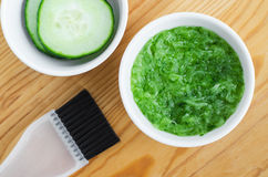 Grated cucumber in a small ceramic bowl for preparing natural facial mask. Homemade cosmetics. Royalty Free Stock Image
