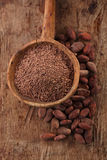 Grated dark chocolate in old wooden spoon on roasted cocoa Stock Photo