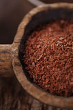 Grated dark 100% chocolate  in spoon on roasted cocoa chocolate Stock Photo