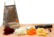 Grated fresh fruits, grater and a knife Royalty Free Stock Images